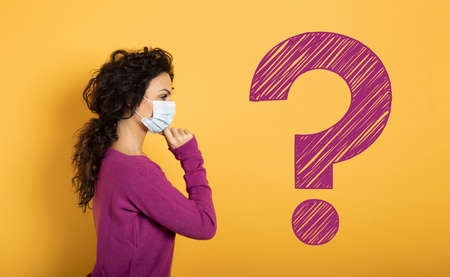 Girl with face mask has a lot of question about covid 19. Yellow background