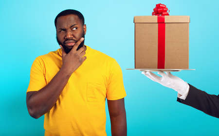 Confused man is suspicious about a gift. concept of options, confusion, indecision
