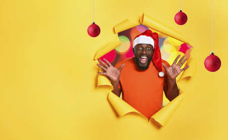 Afro man with hat is happy because is Christmas. Yellow background