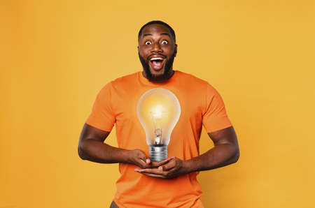 Happy afro man holds a lightbulb with hands. Concept of idea and creativity. Orange background Standard-Bild