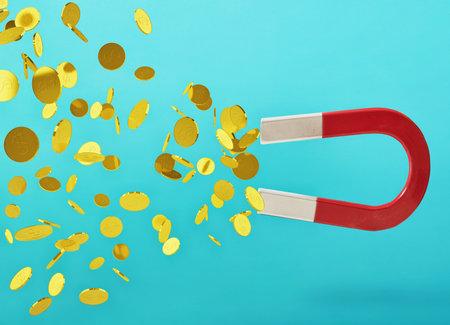 Big magnet captures money. concept of earning success. cyan background