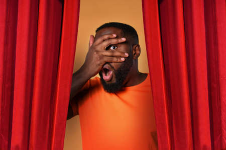 Black curious man try to watch through the hand something. orange background