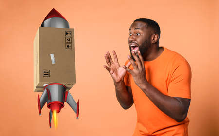 Amazed and shocked expression of a boy who receives a package. orange background Standard-Bild