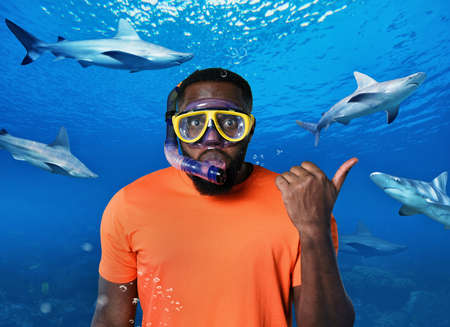 Scared Man with mask underwater surrounded by sharks