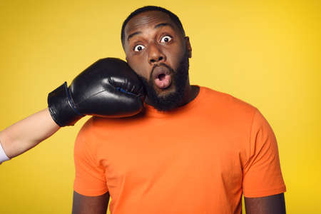 Shocked black man receives a punch from somebodies. yellow background
