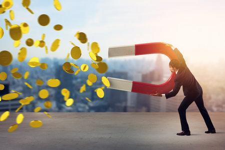 Businessman captures money with a big magnet. concept of earning success. Standard-Bild