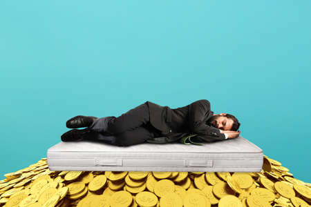 Businessman sleeps serene over a pile of golden coins. concept of wealth and good investment