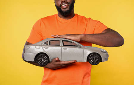 Man holds a small car. concept of buy a new automobile