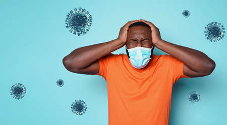 Boy with face mask is tired and stressed of covid 19. cyan background
