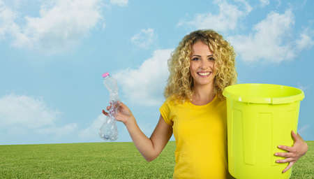 Woman is ready to puts a plastic bottle in the garbage can.