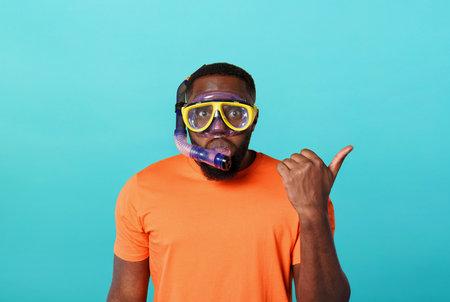 Man with mask ready to swim underwater. yellow background Standard-Bild