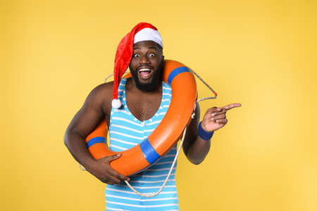 Black man in swimsuit ready to go in a sunny place for christmas. Yellow background