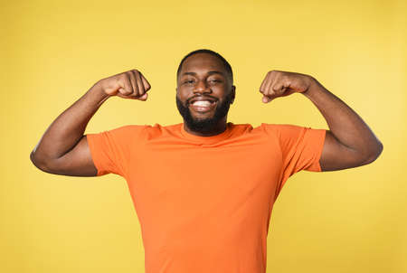 Black man thinks to have strong muscles. yellow background Standard-Bild - 161951280