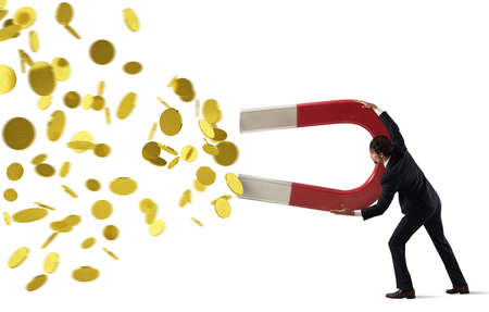 Businessman captures money with a big magnet. concept of earning success. Isolated on white background Standard-Bild