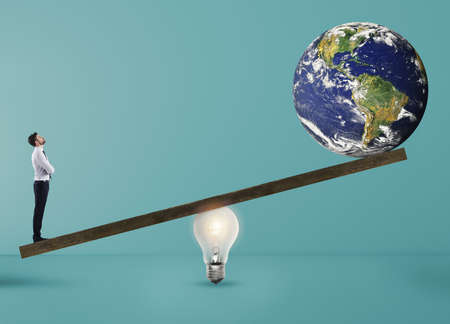 Businessman uses a lightbulb ad lever to lift the World. Earth provided by Nasa. Cyan background