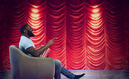 Man sitting on a armchair watches a show in a theatre Standard-Bild