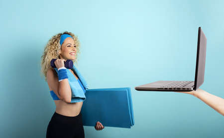 Girl with handlebars ready to start the gym online with a computer. cyan background