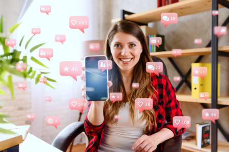 Happy woman shows her smartphone with social network messages, chat and users icons