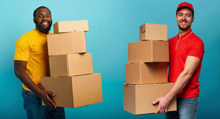 Happy man received a lot of package from courier. cyan background