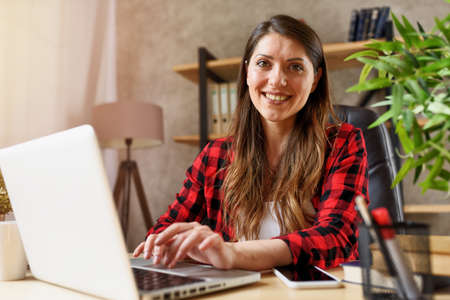 Woman surfs in internet with her laptop. She work at home as smart working Standard-Bild - 162391821
