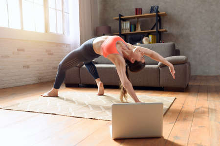 Young woman follows with a laptop a gym exercises. She is at home due to coronavirus codiv-19 quarantine Standard-Bild - 162391823