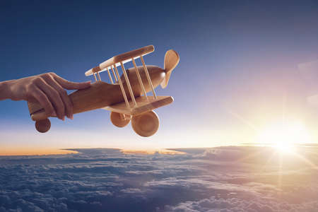 Close up of a vintage wooden toy airplane, held up by one hand, flying above the clouds in the sky