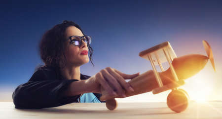 Woman with vintage wooden toy plane dreams of achieving desired goals Standard-Bild