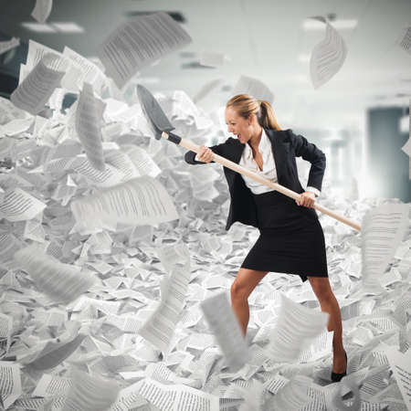 Worker submerged in paperwork makes her way with a shovel Imagens