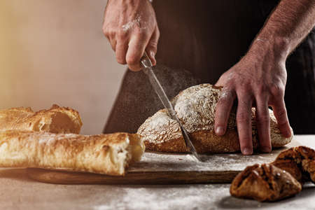 Baker with bread just out of the oven Stock Photo
