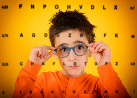 Child tries new glasses to see better. yellow background