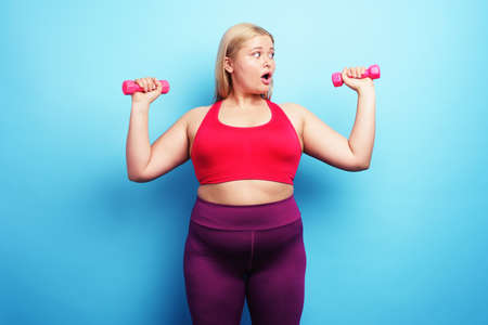 Fat girl does gym but is worried for something. cyan background
