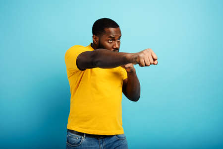 Black man punches and fight against something. cyan background