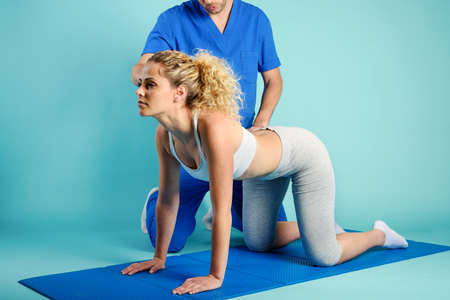 Girl performs exercises with a physiotherapist. Cyan background Standard-Bild
