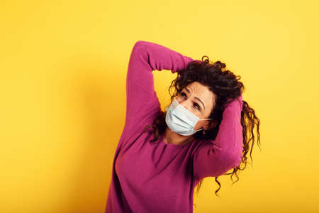 Fearful expression of a woman who is scared to catch the virus. yellow background. Standard-Bild