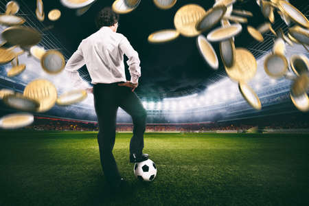 Confident businessman in the center of the soccer field collects a lot of money from the football Standard-Bild