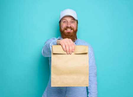 Deliveryman with wondered expression ready to deliver bag with food. cyan background.