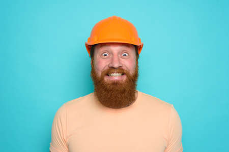 Worker with yellow hat is happy about his work. cyan background