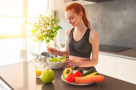 Athletic young red haired woman in the home kitchen eating a healthy salad Standard-Bild