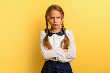 Young girl is unhappy and angry about something. yellow background
