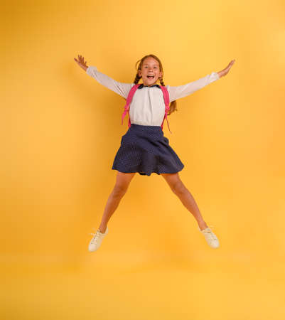 Young girl student jumps high happy for the promotion. Yellow background Standard-Bild