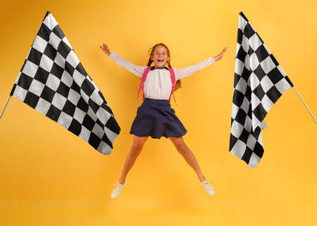 Young girl student jumps high happy for the promotion and reaches the flag. Yellow background