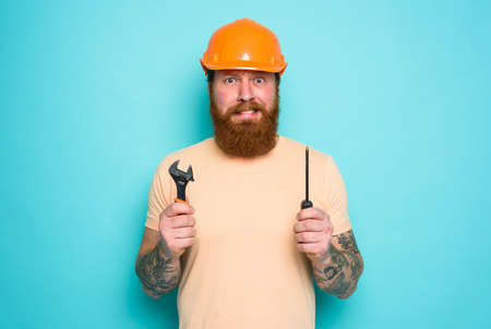 Confused man with screwdriver and spanners. worried and uncertain expression. cyan background Standard-Bild