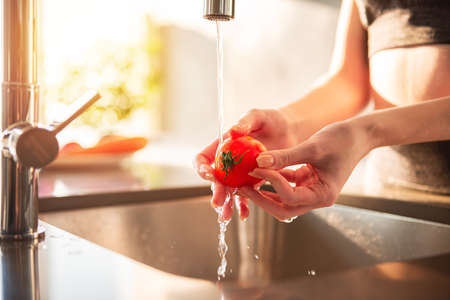 Woman cleans tomatoes in the kitchen in her home illuminated by the sun