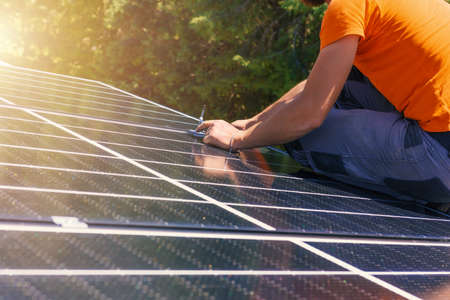 Workers assemble energy system with solar panel for electricity and hot water