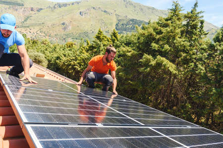 Workers assemble energy system with solar panel for electricity and hot water Banque d'images