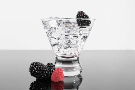 Sparkling beverage in a martini glass with a blackberries and raspberries Stock Photo