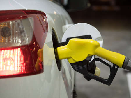 Yellow fuel nozzle in gas station at night Stock Photo