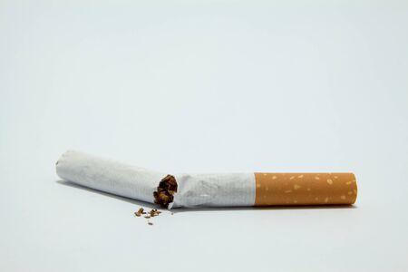 poronienie: Rozrzucone kawałki tytoniu z zerwane papieros samodzielnie na białym tle. Zdjęcie Seryjne