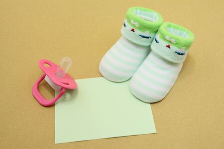 Baby socks with pink pacifier and blank note photo
