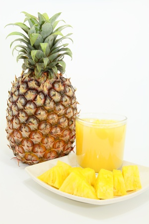 Sliced pineapple with fresh juice and fruit over white